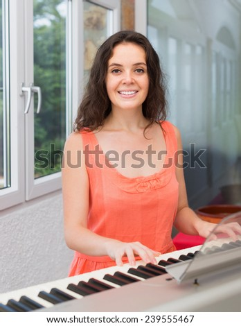 Young woman playing piano at home and smiling  - stock photo