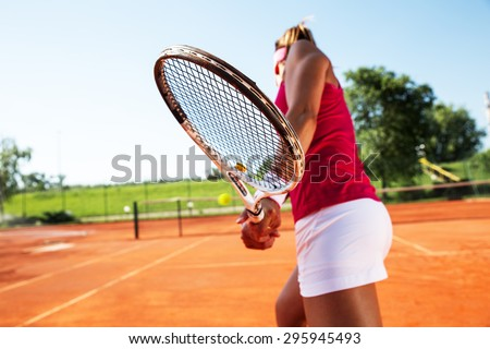 Young woman playing tennis. - stock photo