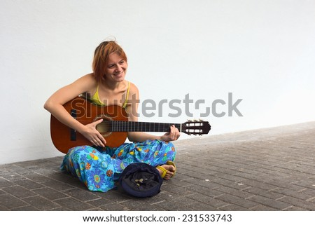 Young woman playing the guitar on the street with a hat containing some coins in front of her  - stock photo