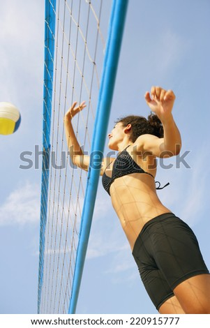 Young woman playing volleyball - stock photo
