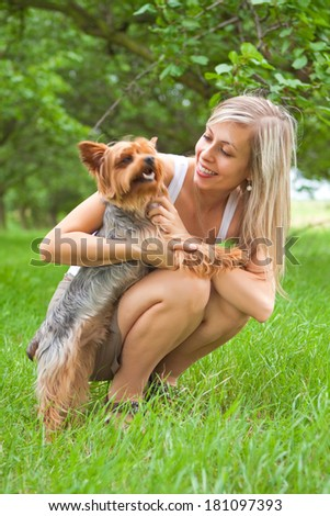 Young woman playing with dog in the park - stock photo
