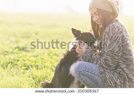 Young woman playing with her border collie dog. concept about animals and people - stock photo