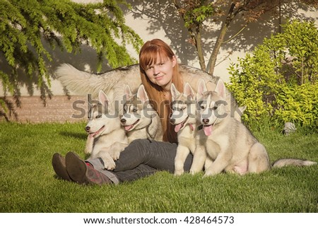 Young woman playing with the dogs. Siberian husky. Puppies. - stock photo