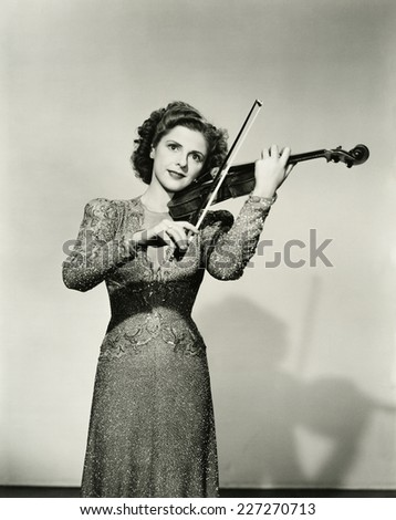 Young woman plays violin - stock photo