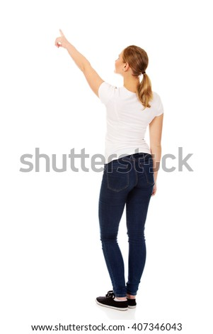 Young woman pointing on copy space or something - stock photo