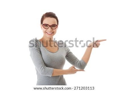 Young woman pointing towards blank space. - stock photo