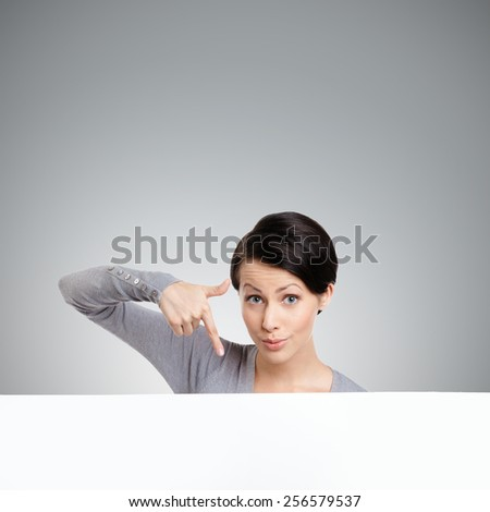 Young woman points down with finger , isolated on grey - stock photo