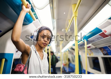 Young woman portrait inside underground in London listening to music with earphones. - stock photo