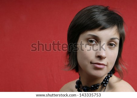 young woman portrait isolated on red background - stock photo