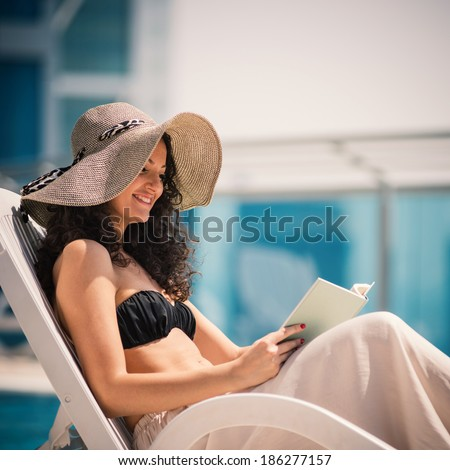 Young woman portrait relaxing and reading a book in swimming pool in Dubai. Filtered image. - stock photo
