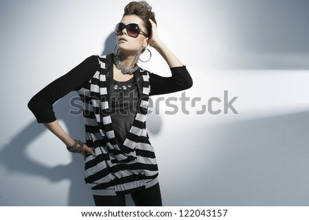 young woman portrait wearing sunglasses on light background - stock photo