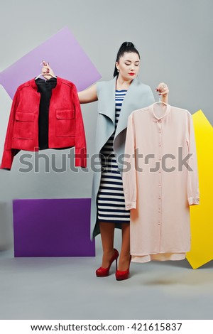 Young woman portrait with blank yellow and purple banner, board on gray isolated holding clothes at hands - stock photo