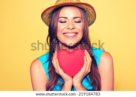 Young woman portrait with closed eyes holding red Heart. Love symbol. - stock photo