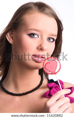 Young woman portrait with heart shaped lollipop. Isolated on white. - stock photo