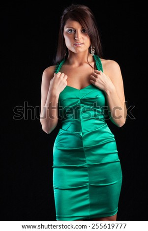 Young woman poses wearing fitted green dress in studio - stock photo