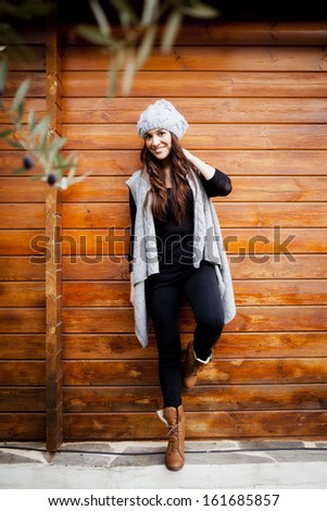 Young woman posing against a wooden wall - stock photo
