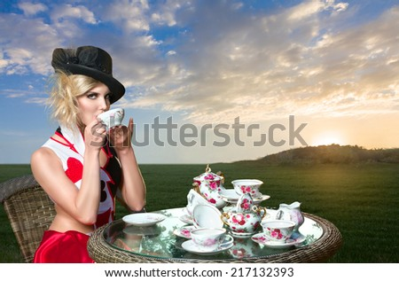 Young woman posing as magnificent card queen from wonderland at mystic tea-party - stock photo