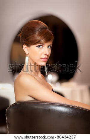 young woman posing elegant at camera with stilis=h hairdo - stock photo