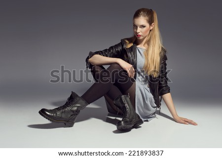 young woman posing in dress and leather jacket and grunge boots - stock photo