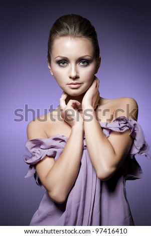 young woman posing in purple dress, studio shot - stock photo