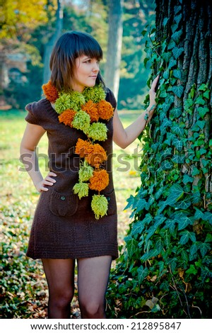 Young woman posing outdoor dressed in handmade knitted dress and scarf. - stock photo