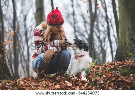 Young woman posing outdoor with her dog in the forest - stock photo