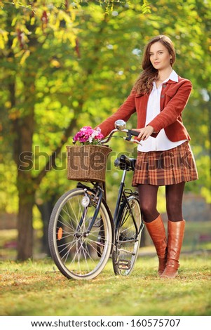 Young woman posing with a bicycle in a park - stock photo