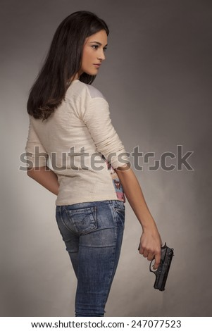 young woman posing with a gun on a gray background - stock photo