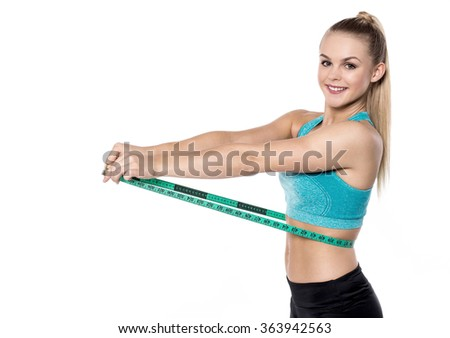 Young woman posing with measuring tape on waist - stock photo