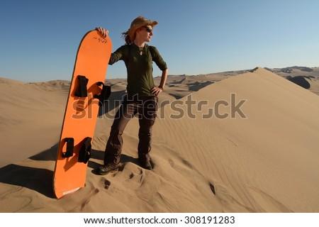 Young woman posing with the sandboard, Oasis of Huacachina, Atacama Desert, Peru - stock photo