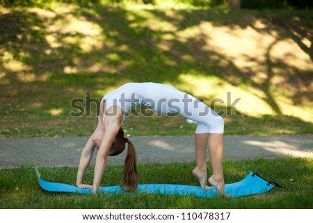 Young woman practices yoga in nature; standing on hands and feet, the bridge pose - stock photo