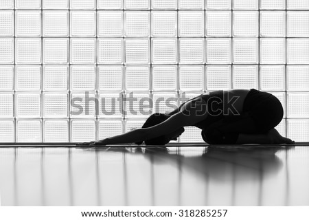Young woman practicing in a yoga studio. Child pose, resting pose. - stock photo