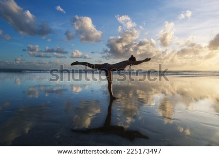 Young woman practicing warrior pose from yoga on the beach at sunset - stock photo