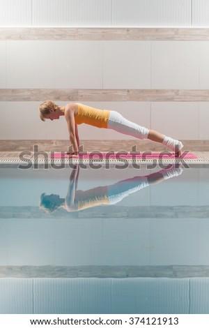 Young woman practicing yoga at swimming pool, Chaturanga Dandasana / Four-Limbed Staff Pose - stock photo