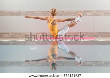 Young woman practicing yoga at swimming pool, Navasana / Variation of Boat pose - stock photo