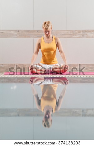 Young woman practicing yoga at swimming pool, Padmasana / Lotus Position - stock photo