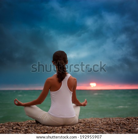 Young Woman Practicing Yoga by the Sea at Sunset. Rear View. Healthy Lifestyle Concept. Instagram Styled Toned Photo. - stock photo