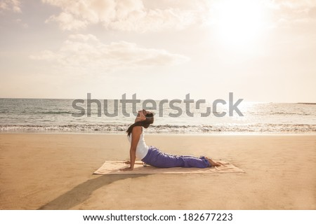 Young woman practicing yoga cobra pose on the beach near the ocean at sunset - stock photo