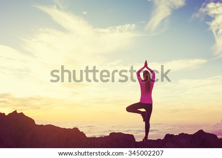 Young Woman Practicing Yoga in the Mountains at Sunset, Healthy Active Lifestyle - stock photo