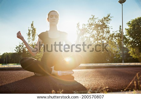 Young Woman Practicing Yoga Meditating On Jogging Track - stock photo