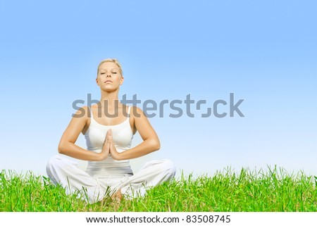 Young woman practicing yoga meditating outdoors with copyspace. - stock photo