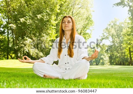 Young woman practicing yoga meditation in the park. - stock photo