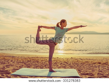 Young woman practicing yoga on mat on sand beach near the sea on sunset, woman in stretching balance pose - stock photo