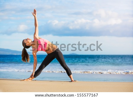 Young woman practicing yoga on the beach at sunset - stock photo