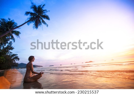 Young woman practicing yoga on the beach at sunset. - stock photo