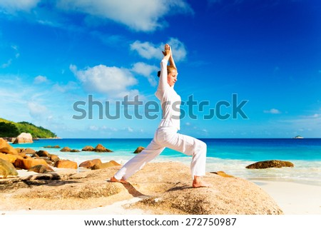 Young woman practicing yoga on the rock - stock photo