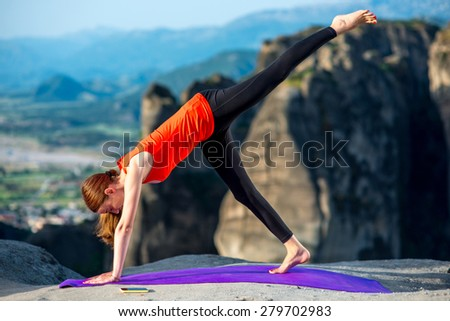 Young woman practicing yoga on the top of mountain - stock photo