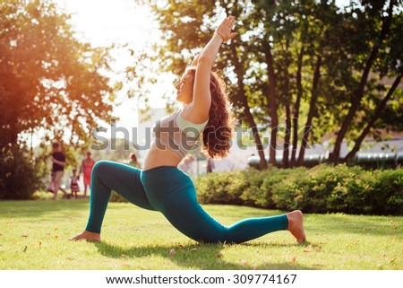 Young woman practicing yoga outdoor in park. Toned picture - stock photo