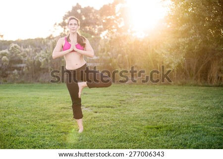 Young woman practicing yoga outside in the grass - stock photo