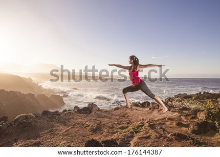 Young woman practicing yoga warrior pose near the ocean at sunset - stock photo